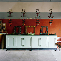 A dining room with stone walls painted in grey and terracotta red. Four wrought-iron pieces, four wall ceramics and empty picture frames are displayed in an orderly fashion above a white painted sideboard.