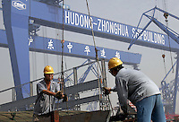 Two Chinese workers unloads materials under the giant cargo lifts at the Hudong Zhonghua Shipbuilding Co., LTD in Shanghai, China. China is the world's third largest shipbuilding nation after South Korea and Japan. While growing international interest in its lower building cost and domestic tanker demand to fulfill the country's hunger for energy is likely to push the country to the top position, the rapidly increasing price of steel has also undercut the industry's profitability..