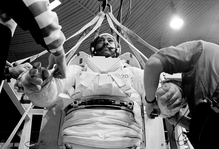 Image copyright John Angerson. <br /> STS-72 mission training.<br /> Astronaut Winston E. Scott is lifted by crane into the neutral-buoyancy diving pool. During his NASA career, he logged a total of 24 days, 14 hours, and 34 minutes in space, including three spacewalks totalling 19 hours and 26 minutes. He was also an experienced naval pilot.<br /> Neutral Buoyancy Laboratory (NBL). Johnson Space Center, Houston, Texas.