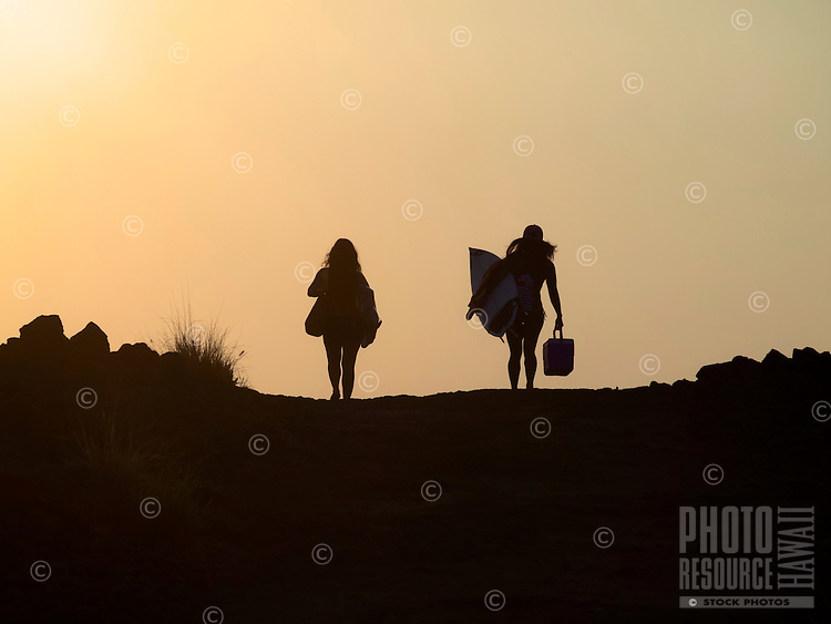 Surfer silhouette: two surfers walking with their surfboards towards a setting sun at Mahai'ula Beach, Kekaha Kai State Park, North Kona, Hawai'i Island.