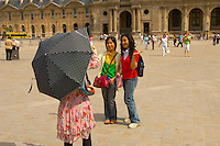 Oriental girl tourists having their photo taken at the Louvre Paris