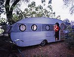 Woman posing in front of a vintage travel trailer.