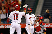 Alberto Callaspo #6 of the Los Angeles Angels welcomes teammate Hank Conger #16 after Conger's home run during a game against the St. Louis Cardinals at Angel Stadium on July 3, 2013 in Anaheim, California. (Larry Goren/Four Seam Images)