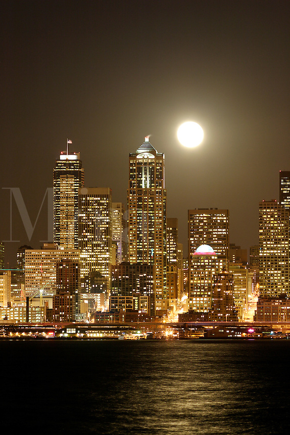 Full moon rising over Seattle city skyline at night, Seattle, Washington, US