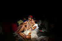 CHINA. Beijing. A couple sat amongst people watching the opening ceremony of the Beijing 2008 Summer Olympics. 2008