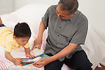 3 year old preschool age boy with grandfather looking at book, read to
