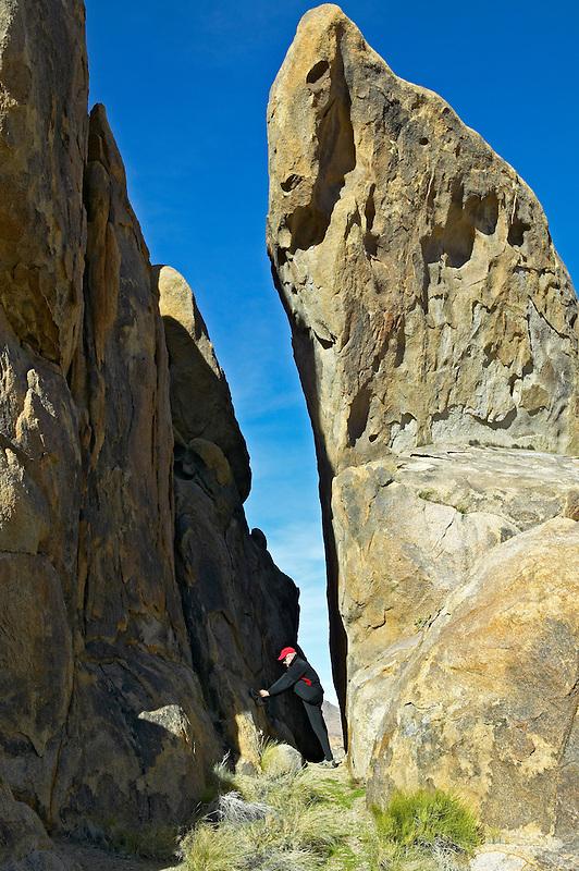 Hiker tying shoes near monolith rocks in Alabama Hills, California