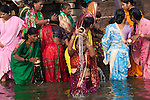 Pilgrims seek purification in the waters of the Ganges River, Varanasi, India.