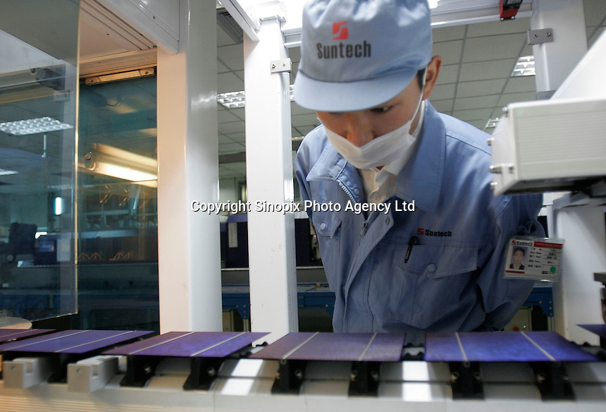 A worker inspects solar power battery cells at the Suntech factory in Wuxi, China. Suntech is one of the world's top 10 manufacturers of PV cells based on production output..