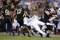 WINSTON-SALEM, NC - SEPTEMBER 13: Jamie Newman #12 of Wake Forest University is sacked by Tyrone Hopper #42 of the University of North Carolina during a game between University of North Carolina and Wake Forest University at BB