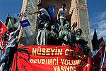 """Young protesters take a police shield emblazoned with the word Katil--""""killer"""" in English--on top of the Monument to the Republic in Taksim Square, Istanbul, Turkey, June 1, 2013. The monument depicts Mustafa Kemal Ataturk and was inaugurated in 1928, five years after the republic was founded. What started as a peaceful sit-in to save a small park near Taksim Square from being turned into a shopping mall has turned into large-scale anti-government demonstrations in cities across Turkey."""