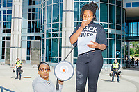 """Rally organizer Anaysha Benalfew, 10, (standing) speaks to the crowd about equality and fear for black lives outside the Boston Police Department Headquarters during the """"Peaceful Children's March: Be the Change"""" demonstration in support of Black Lives Matter in Boston, Massachusetts, on Sun., June 7, 2020. Jay'dha Rackard, 11, holds the bullhorn while Benalfew speaks. The children's march was organized by siblings Naheem, 7, and Anaysha Benalfew, 10. The demonstration is part of a weeks-long nationwide response to the killing of George Floyd by Minneapolis police on May 25, 2020. The march started near the Nubian Square bus depot and continued to the nearby Boston Police Department headquarters, where marchers knelt for 8 minutes and 46 seconds, the time that police officers knelt on George Floyd's neck during his killing. A number of children, mostly people of color, then spoke about how people should be treated equally and how they wished they didn't have to grow up fearful that a police officer would kill them or their loved ones."""