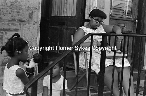 African American mother and children, the girl is playing with a white doll. Mother is listening to music on a portable record player she has on her lap some singles records, 45 rpm discs. They are on the porch of their home.   New Brunswick, New Jersey,1969,