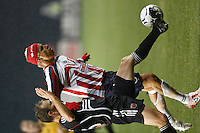D. C. United midfielder (26) Bryan Namoff pokes the ball away from CD Guadalajara forward (1) Adolfo Bautista during the first game of the CONCACAF Champions' Cup  Semifinal Series between CD Guadalajara of Mexico and D. C. United of the USA at Robert F. Kennedy Memorial Stadium, Washington, D. C., on March 15, 2007. DC United and CD Guadalajara played to a 1-1 tie.
