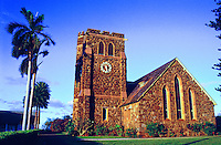 Sunlight shines on the Makawao Union Church and nearby palm trees.