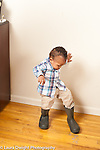 17 month old toddler boy putting boots belonging to big brother or father