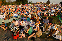 Fans gather each summer for the free Charlotte Symphony Summer Pops concert series at SouthPark Mall in Charlotte, NC. Spectators enjoy picnicking on the green grass while listening to music fill the air.