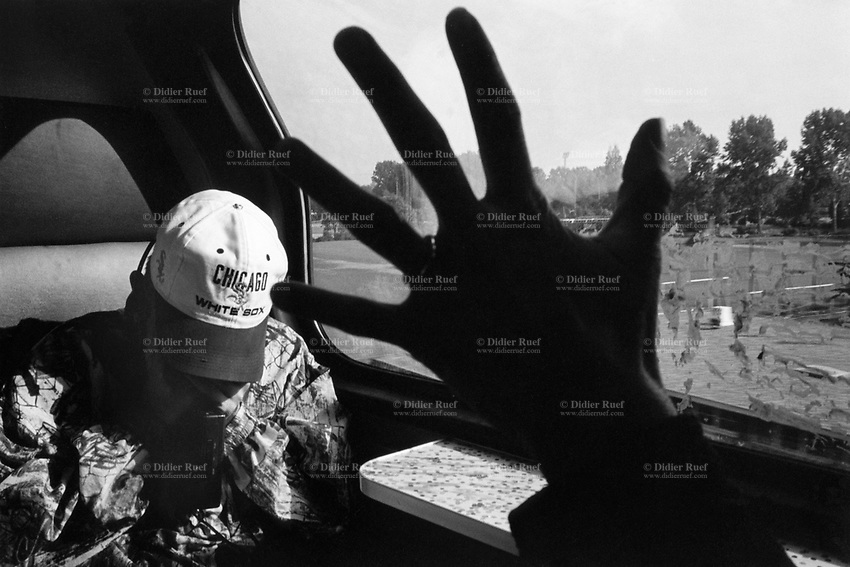 Holland. Train ride in the countryside outside Amsterdam. A young man seats by the window. He wears a cap from the Chicago White Sox (a professional baseball team). Passenger's hand silhouette. © 1995 Didier Ruef