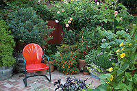 Red chair in small space patio garden with containers of organic vegetables and herbs