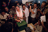 Larkana, Pakistan<br /> November 16, 1988<br /> <br /> Benazir Bhutto casts her ballot at a voting station in Larkana.<br /> <br /> Benazir Bhutto is the eldest child of former Pakistan President and Prime Minister Zulfikar Ali Bhutto. She found herself placed under house arrest in the wake of her father's imprisonment and subsequent execution in 1979. In 1984 she became the leader in exile of the Pakistan Peoples Party (PPP), her father's party, though she was unable to make her political presence felt in Pakistan until after the death of General Muhammad Zia-ul-Haq. <br /> <br /> On 16 November 1988 Benazir's PPP won the largest bloc of seats in the National Assembly. Bhutto was sworn in as Prime Minister in December, at age 35 she became the first woman to head the government of a Muslim-majority state in modern times. <br /> <br /> She was removed from office 20 months later under orders of then-president Ghulam Ishaq Khan for alleged corruption. Bhutto was re-elected in 1993 but was again removed by President Farooq Leghari in 1996, on similar charges. Bhutto went into self-imposed exile in Dubai in 1998, until she returned to Pakistan on October 2007, after General Musharraf granted her amnesty and all corruption charges withdrawn.