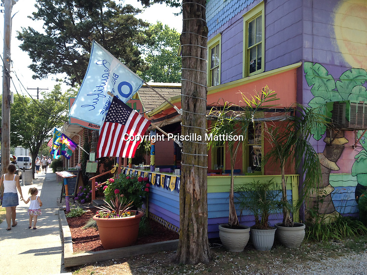 Rehoboth Beach, Delaware - <br /> June 21, 2012:  A woman walks with a girl down the sidewalk in front of the brightly-painted Iguana Café.
