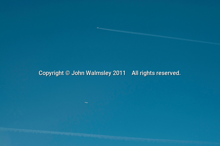 A contrail or water condensation trail from an aircraft's jet engines, high above the Southeast of England.  The much lower jet has none.