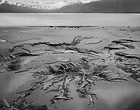 """""""Mud At Low Tide in the Cook Inlet"""" <br /> Alaska<br /> <br /> Low tide often reveals surprises and this black and white photo shows one of those. Driving on Alaska's Seward Highway south of Anchorage took me to a pullout at Beluga Point during low tide in the Cook Inlet. The scenery across the water was impressive and was enhanced by patterns in the mud formed by water flowing as the tide dropped. Atmospheric haze across the inlet was not reduced since I wanted the mountains to feel more distant. To further develop the feeling of depth in the photograph, I developed the film N+1 to enhance foreground texture."""