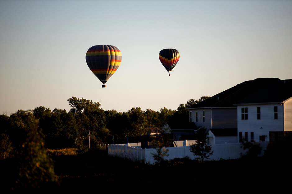 Hot air balloons float over a residential neighborhood near the airport in Bloomington, Indiana on Saturday, Sept. 19, 2020. (Photo by James Brosher)