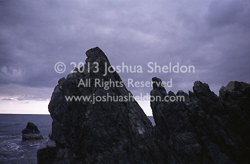 Storm clouds over rocky shoreline<br />