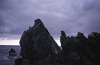 Storm clouds over rocky shoreline<br />