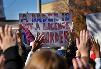 STAFF PHOTO BEN GOFF  @NWABenGoff -- 11/25/14 A demonstrator holds a sign reading 'A badge us not a license to murder' as other hold up their hands chanting 'Hands up, don't shoot' during a protest organized by the OMNI Center for Peace, Justice & Ecology in front of the Washington County Courthouse in Fayetteville on Tuesday Nov. 25, 2014. The demonstration was in response to the decision Monday night by the St. Louis County grand jury not to indict police officer Darren Wilson, who fatally shot Michael Brown in Ferguson, Mo.