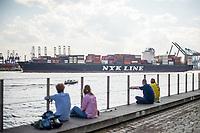 Menschen sitzen bei sonnigem Fruehlingswetter im Hamburger Hafen und geniessen das gute Wetter. Im Hintergrund wird ein Containerschiff geschleppt.<br /> 9.5.2020, Hamburg<br /> Copyright: Christian-Ditsch.de<br /> [NUR FUER REDAKTIONELLE ZWECKE! Werbung nur auf Anfrage beim Fotografen.Inhaltsveraendernde Manipulation des Fotos nur nach ausdruecklicher Genehmigung des Fotografen. Vereinbarungen ueber Abtretung von Persoenlichkeitsrechten/Model Release der abgebildeten Person/Personen liegen nicht vor. NO MODEL RELEASE! Don't publish without copyright Christian-Ditsch.de, Veroeffentlichung nur mit Fotografennennung, sowie gegen Honorar, MwSt. und Beleg. Konto: I N G - D i B a, IBAN DE58500105175400192269, BIC INGDDEFFXXX, Kontakt: post@christian-ditsch.de<br /> Bei der Bearbeitung der Dateiinformationen darf die Urheberkennzeichnung in den EXIF- und  IPTC-Daten nicht entfernt werden, diese sind in digitalen Medien nach §95c UrhG rechtlich geschuetzt. Der Urhebervermerk wird gemaess §13 UrhG verlangt.]