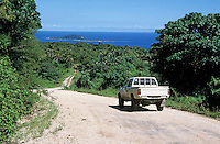 Pick up truck travelling on a dirt road leading towards the ocean with hat island in the background, Efate Island, Vanuatu.