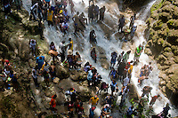 Thousands of Haitians, both followers of Catholicism and Voodoo, bathe in the waterfall during the annual religious pilgrimage in Saut d'Eau, Haiti, July 16, 2008. Every year in summer thousands of pilgrims from all over Haiti make the religious journey to the Saut d'Eau waterfall (100km north of Port-au-Prince). It is believed that 150 years ago the spirit of Virgin Mary (Our Lady of Mount Carmel) has appeared on a palm tree close to the waterfall. This place became a main pilgrimage site in Haiti since then. Haitians wearing only underwear perform a bathing and cleaning ritual under the 100-foot-high waterfall. Voodoo followers (many Haitians practise both voodoo and catholicism) hope that Erzulie Dantor, the Voodoo spirit of water, manifest itself and they get possessed for a short moment, touched by her presence.