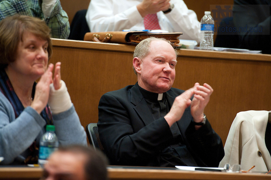 """November 18, 2011; Rev. Timothy Scully, C.S.C., director of Institute for Educational Initiatives; Professor, applauds at the close of New Jersey Gov. Chris Christie's keynote address during a daylong symposium, titled """"Educational Innovation and the Law"""" in the Patrick F. McCartan Courtroom at the Notre Dame Law School. Photo by Barbara Johnston/University of Notre Dame."""