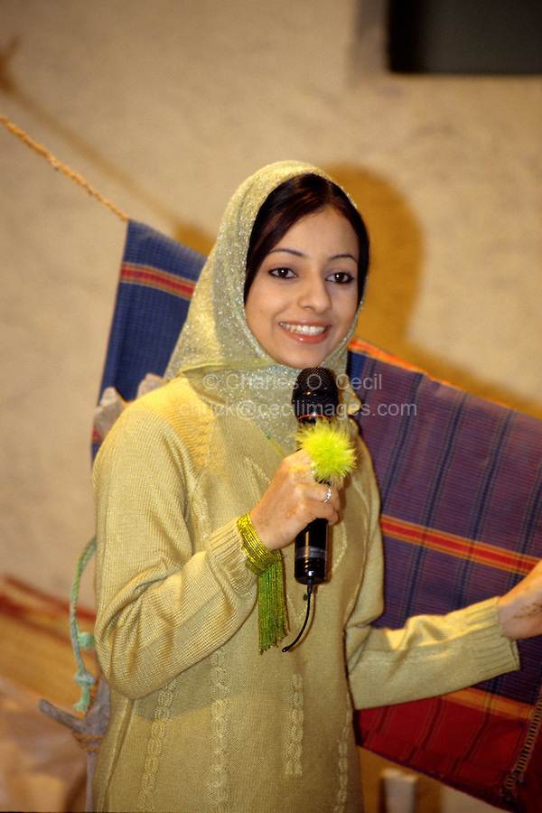 Muscat, Oman, Arabian Peninsula, Middle East - Woman TV Journalist Giving Commentary at Muscat Festival.