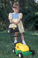 A little girl playing with a toy lawn mower.