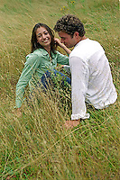 Couple sitting & relaxing in grass<br />