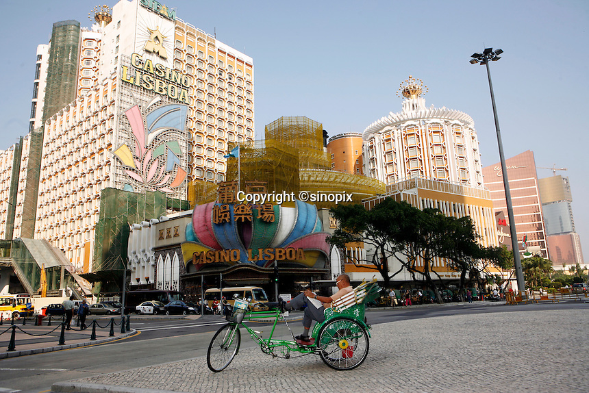 A cyclo driver rests on the street in front of the Casino Lisboa, Macau.