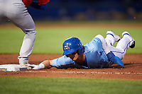 Omaha Storm Chasers Bobby Witt Jr. (7) slides into first base on a pickoff attempt during a game against the Iowa Cubs on August 14, 2021 at Werner Park in Omaha, Nebraska. (Zachary Lucy/Four Seam Images)