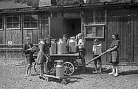 Die Kinder holen Milch für die Familie und für die Schulspeisung ab, Deutschland 1940er Jahre. Children fetching milk for home and school lunch, Germany 1940s.
