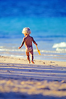 A blond toddler with sand stuck on his bare bottom runs toward the water at Lanikai Beach.