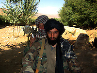 A  commander and one of his foot soldiers from the Wardak Mobile Patrol Unit sit on a chinese motorcycle before they go out on patrol armed with an RPG [rocket propelled grenade]