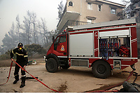 Pictured: A fireman and a fire truck in the village of Kalamos.<br /> Re: A forest fire has been raging in the area of Kalamos, 20 miles east of Athens in Greece. There have been power cuts, country houses burned and children camps evacuated from the area.