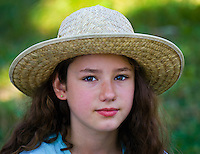 Young girl with curly hair wearing wide brim straw hat.