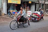 Myanmar, Burma, Mandalay.  Street Scene.  Bicycle Rider, Used Clothing Vendor.