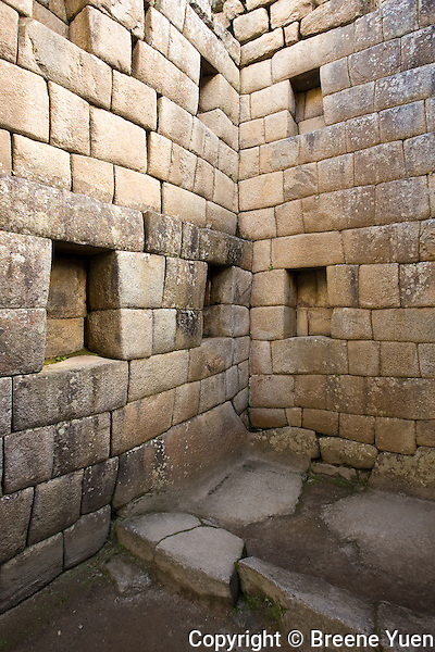 The remains of a home in Machu Picchu.  That is a bed area in the corner floor area.  Note the trapezoid shaped cubby-holes.