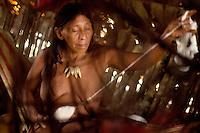 Nawade Caiga, 64, spins cotton, inside a palm leaf house in the Waorani (Huaroni) community of Cononaco Chico.