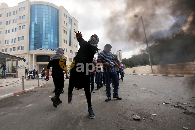 Female Palestinian protester throws stones at Israeli security forces during clashes in Beit El, near the West Bank city of Ramallah, on October 8, 2015. New violence rocked Israel and the Israeli occupied West Bank, including an incident in which men thought to be undercover Israeli police opened fire on Palestinian stone throwers they had infiltrated, wounding three of them. Photo by Shadi Hatem