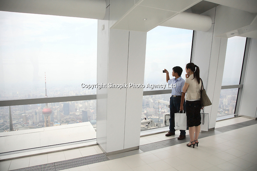 Visitors look at the cityscape below while standing in the Shanghai World Financial Center's observation decks in Shanghai, China..